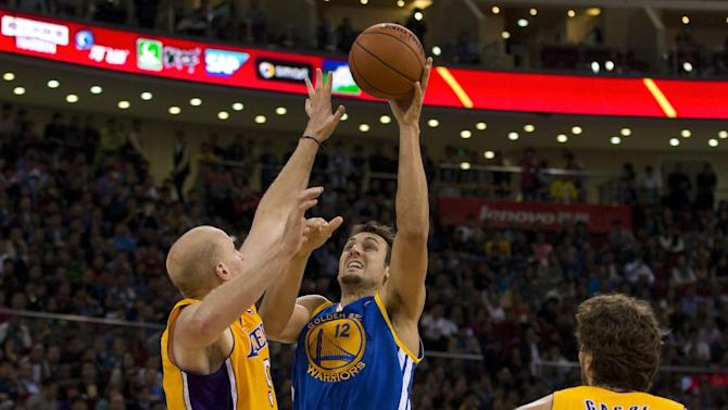 Andrew Bogut of the Golden State Warriors, center, shoots over Chris Kaman of the LA Lakers during their NBA Global Game at the Wukesong Stadium in Beijing Tuesday, Oct. 15, 2013. The Warriors defeated Lakers 100-95