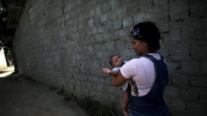 Jackeline, 26, holds her son Daniel who is 4-months old and born with microcephaly, as they walk on the street toward their house in Olinda