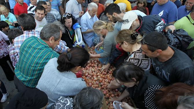 People collect onions distributed by Greek street fruit and vegetable market vendors during a protest in Athens, Wednesday, May 15, 2013. The union of Greek farmers markets went on strike, Wednesday, as protesters set up stands and started distributing vegetables to a fast growing crowd. The market vendors are the latest professional group in Greece to protest a sweeping market liberalization drive demanded by rescue creditors,  and timed their protest to draft legislation due to be voted in parliament to implement the new guidelines. (AP Photo/Thanassis Stavrakis)