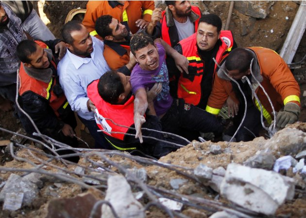 Members of the Palestinian Civil Defense help a survivor after he was pulled out from under the rubble of his destroyed house after an Israeli air strike in Gaza City