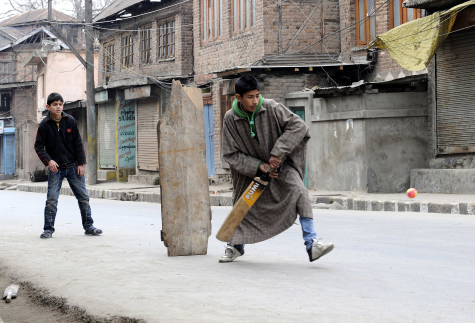 Indian Kashmiri youths play cricket on a