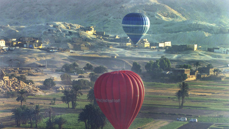 FILE - In this Wednesday, May 24, 2006 file photo, tourists take a hot air balloon tour over Luxor, Egypt. A hot air balloon flying over Egypt's ancient city of Luxor caught fire and crashed into a sugar cane field outside al-Dhabaa village, just west of the city of Luxor,  Egypt, Tuesday, Feb. 26, 2013, killing at least 19 foreign tourists, a security official said. (AP Photo/Mohammed Anan, File)