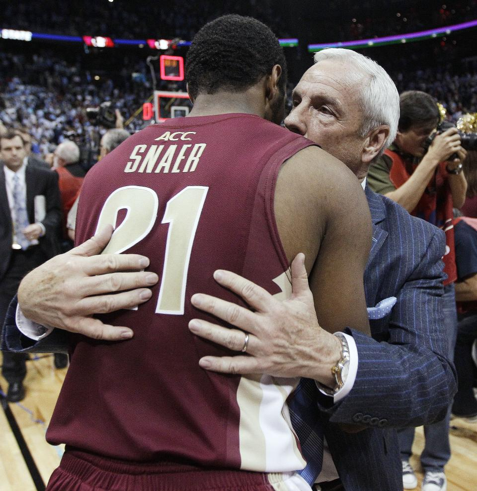 North Carolina coach Roy Williams embraces Florida State guard Michael Snaer after an NCAA college basketball game in the final of the Atlantic Coast Conference men's tournament, Sunday, March 11, 2012, in Atlanta. Florida State won 85-82. (AP Photo/Chuck Burton)
