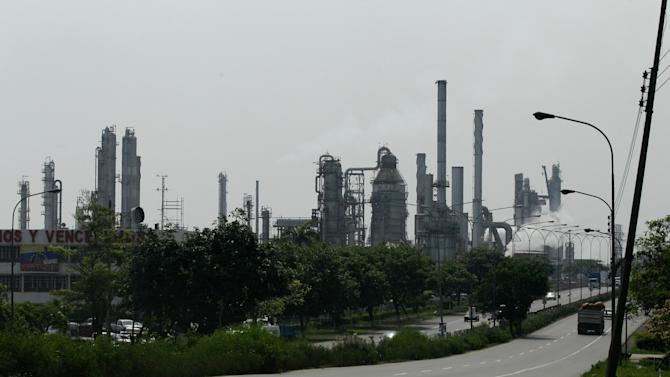 In this April 25, 2013, motorists drive past the El Palito refinery, near Moron, Venezuela. The oil flowing from the El Palito refinery sells for more than five times what it cost when President Hugo Chavez took office in 1999. Yet when Chavez died in March he left Venezuela's cash cow, its state-run oil company, in such dire straits that analysts say $100-a-barrel oil may no longer be enough to keep the country afloat barring a complete overhaul of a deteriorating petroleum industry. (AP Photo/Fernando Llano)