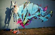 A street artist works on a new piece on a section of wall near Westbourne Park in north London on March 10, 2012. Far from London's beaten tourist track, a group of visitors is staring keenly at the graffiti-covered gates to an abandoned construction site