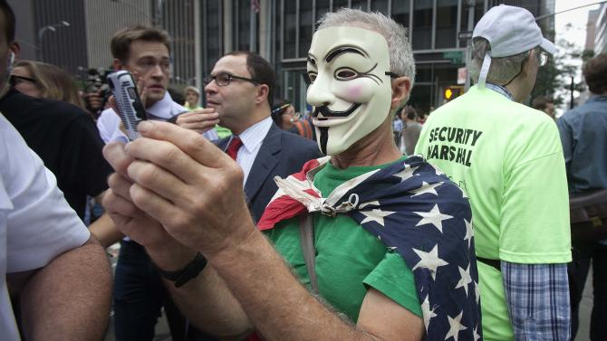 "A protester in an 'Anonymous' mask and wrapped in an American flag takes part in the ""People's Climate March"" down 6th Ave. in the Manhattan borough of New York"