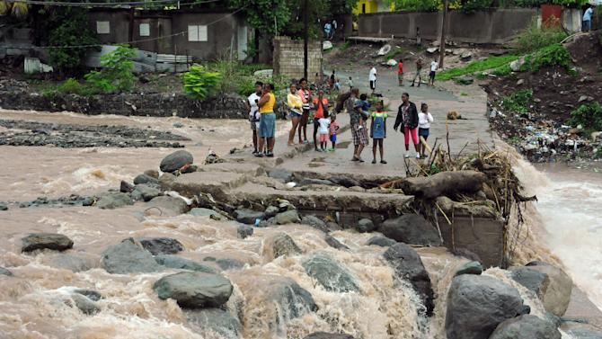 Residents stand on a bridge that was previously destroyed in 2008 by Tropical Storm Gustav, while watching Hope River swell in the village of Kintyre, near Kingston, Jamaica, after the passing of Hurricane Sandy, Thursday, Oct. 25, 2012. Sandy, which made landfall Wednesday afternoon near Kingston, crossed over Jamaica killing an elderly man when a boulder crashed into his clapboard house, police said. (AP Photo/Collin Reid)