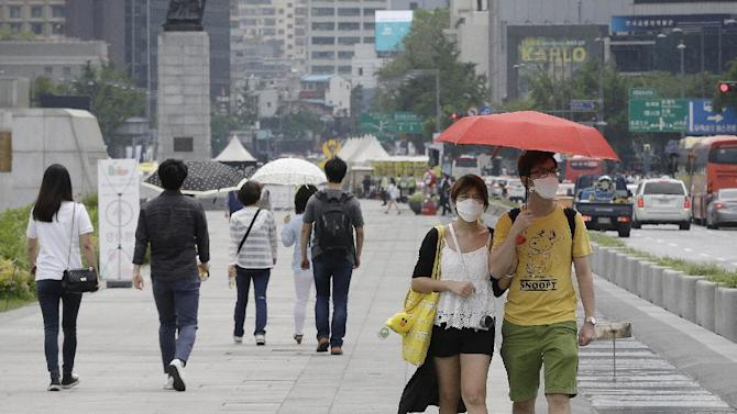 A couple wears masks as a precaution against Middle East Respiratory Syndrome (MERS) virus as they walk on a street in Seoul, South Korea, Tuesday, June 2, 2015. South Korea on Tuesday confirmed the country's first two deaths from MERS as it fights to contain the spread of the virus that has killed hundreds of people in the Middle East. (AP Photo/Ahn Young-joon)