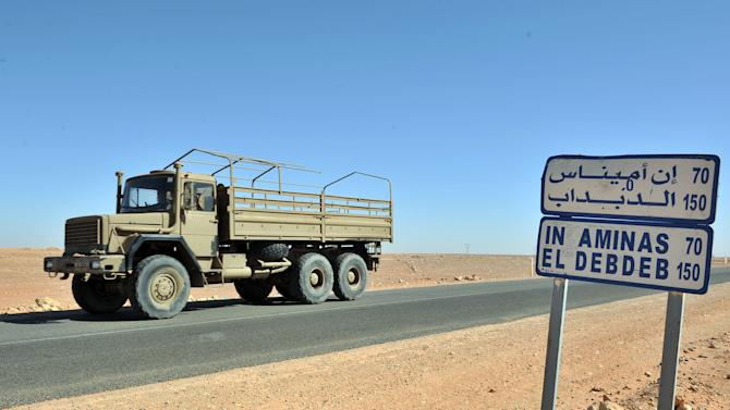 An Algerian military truck drives past a road sign indicating the city of Ain Amenas where hostages have been kidnapped by islamic militants at a gas plant , Friday, Jan. 18, 2013 The hostage crisis in the remote desert of Algeria is not over, Britain said Friday, after an Algerian raid on the gas plant to wipe out Islamist militants and free their captives from at least 10 countries unleashed bloody chaos. (AP Photo/Anis Belghoul)