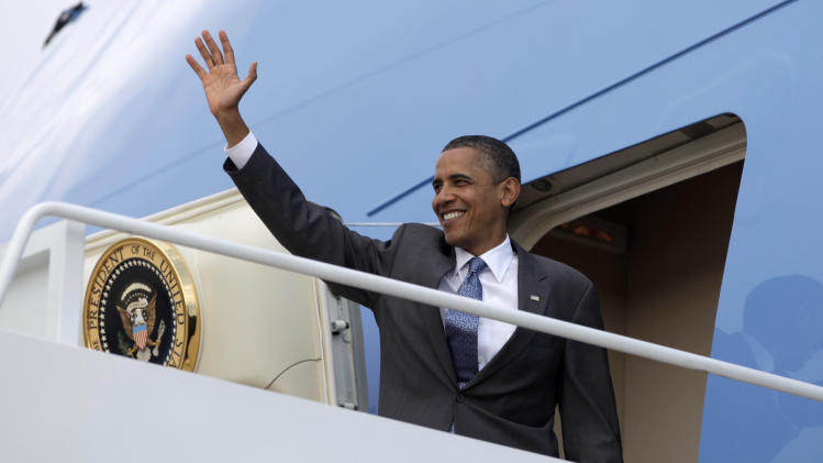 President Barack Obama waves as he boards Air Force One at Andrews Air Force Base, Md., Thursday, Aug. 18, 2011, en route to Martha's Vineyard for a family vacation.  (AP Photo/Carolyn Kaster)