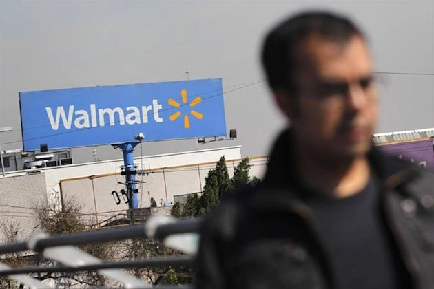 A person walks near a Wal-Mart billboard in Mexico City January 11, 2013. REUTERS/Edgard Garrido/Files