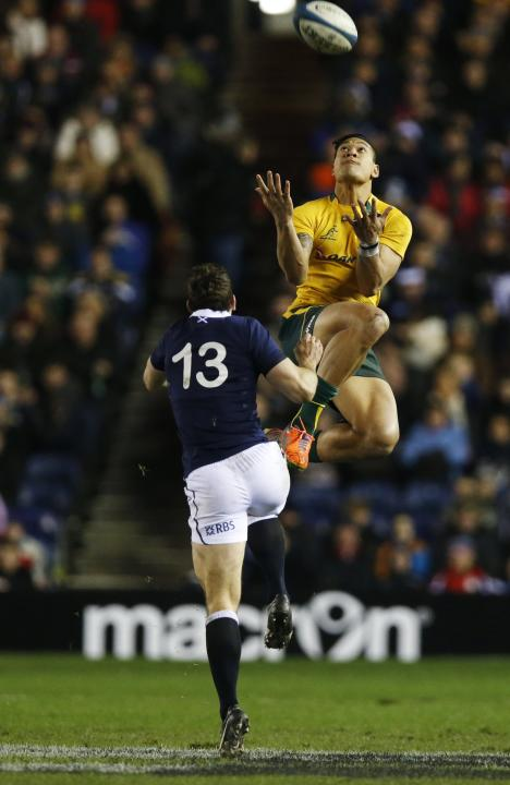Australia's Folau is challenged by Scotland's De Luca during their rugby union international test match in Edinburgh
