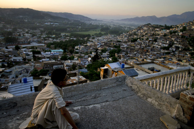 FILE - In this May 15, 2011 file photo, Ali Raza sits on the rooftop of his house as he views the city of Abbottabad, Pakistan. Pakistani officials say the government plans to build a recreation compl