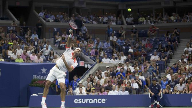 Federer of Switzerland serves to Darcis of Belgium during their second round match at the U.S. Open Championships tennis tournament in New York