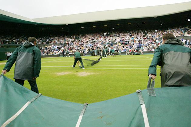 The net is pulled down, as ground staff pull rain covers onto the Centre Court, as rain interupts play on the seventh day of the All England Lawn Tennis Championships, at Wimbledon, Monday, June 30, 2