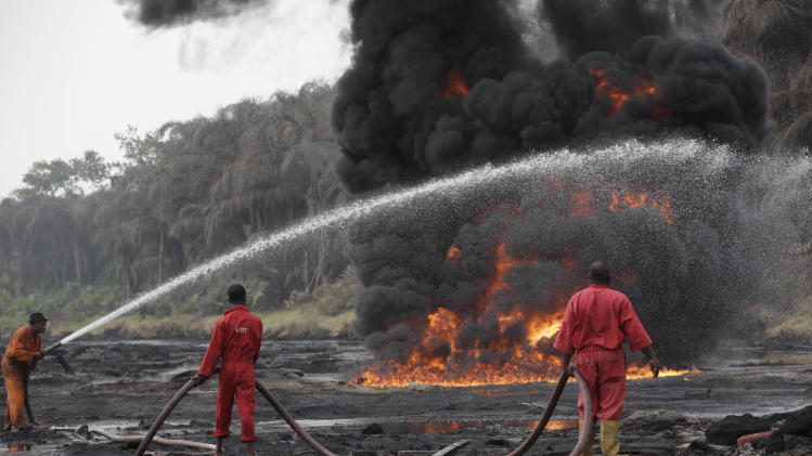Fire fighters try to contain flames a from a burning oil pipeline in Ijeododo in the outskirts of  Lagos, Nigeria  Thursday, Dec. 20, 2012. The oil pipeline belonging to Nigeria National Petroleum Cooperation exploded near Nigeria's largest city as thieves tried to siphon oil from it  Monday. (AP Photo/Sunday Alamba)