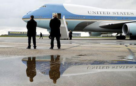 Secret Service agents are reflected in a puddle as U.S. President Barack Obama arrives to board Air Force One at Stansted Airport in Stansted