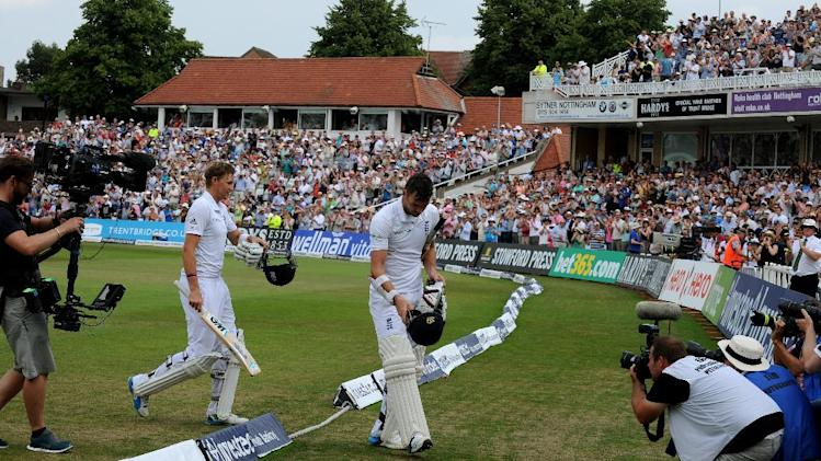 England's Joe Root, second left, and James Anderson leave the field for a lunch break, during day four of the first Test between England and India at Trent Bridge cricket ground, Nottingham, England, Saturday, July 12, 2014. (AP Photo/Rui Vieira)