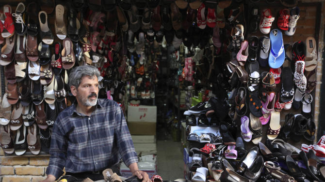 In this picture taken on Sunday, May 4, 2013, an Iranian shoe seller stands in his shop in the old bazaar of the eastern city of Birjand, Iran. When struggling families in the eastern Iranian city of Birjand take measure of Mahmoud Ahmadinejad's presidency in its waning weeks, it's not about his browbeating oratory against the West or his battles with Iran's ruling clerics. Instead, it's the rows of simple two-story homes on the city's outskirts that sharply improved their lives. (AP Photo/Vahid Salemi)