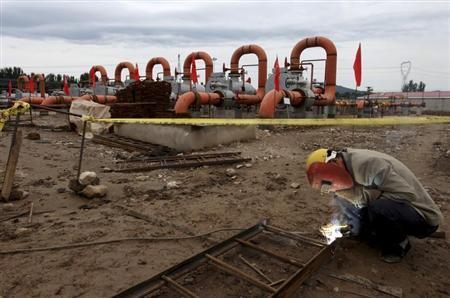 A labourer welds a steel frame next to natural gas pipes at a receiving terminal on the outskirts of Beijing