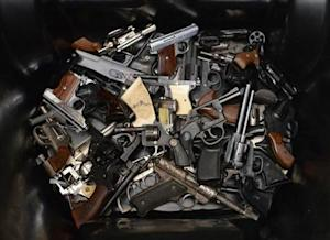 A pile of handguns are placed in a trash bin after they were surrendered during a gun buyback program in Los Angeles, California