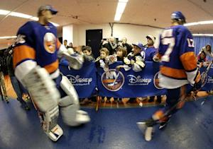 Young fans look on as New York Islanders goalie Anders Nilsson (45), of Sweden, and left wing Matt Martin (17) walk by on their way to the ice before the third period of an NHL hockey game against the Detroit Red Wings, Friday, Nov. 29, 2013, in Uniondale, N.Y. The Red Wings won 5-0