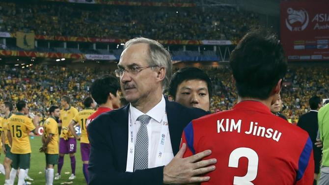 South Korea's coach Uli Stielike consoles player Kim Jin-su after their Asian Cup final soccer match against Australia at the Stadium Australia in Sydney