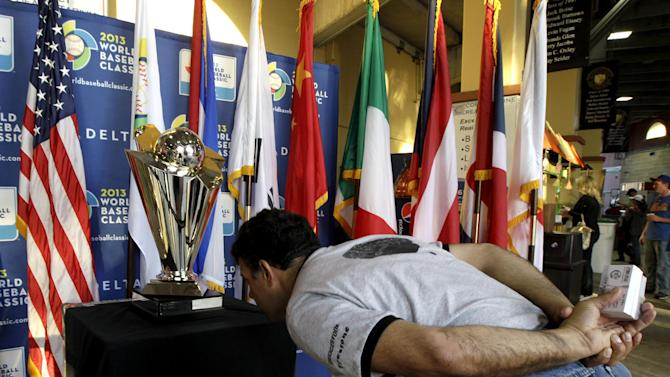 Don Neil, of Ft. Lauderdale, Fla., inspects the writing on the World Baseball Classic trophy before an exhibition baseball game between Venezuela and the Miami Marlins, Tuesday, March 5, 2013, in Jupiter, Fla. (AP Photo/Julio Cortez)