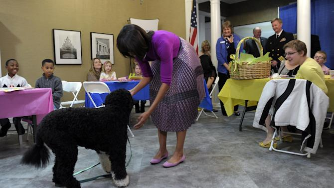 First lady Michelle Obama shows off the Obama family dog, Bo, during her visit to the Fisher House, located at Walter Reed National Military Medical Center in Bethesda, Md., Wednesday, March 20, 2013, for a pre-Easter celebration with military families and children. (AP Photo/Susan Walsh)