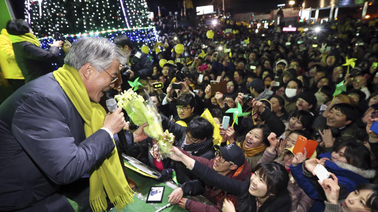 Opposition Democratic United Party's Presidential Candidate Moon Jae-in receives a bouquet of flowers from a supporter during his campaign in Daegu, South Korea, Tuesday, Dec. 18, 2012. South Korea's presidential election is scheduled for Dec. 19. (AP Photo/Yonhap. Lee Jae-hyuck)  KOREA OUT