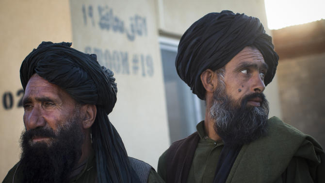 In this Oct. 22, 2012 photo, Afghan men gather at a local police station trying to get permission to gather for a demonstration in Lashkar Gah, Helmand province, Afganistan. In southern Helmand province, one of Afghanistan's deadliest battlefields, angry residents say 11 years of war has brought them widespread insecurity. Development that was promised hasn't materialized and the Taliban's rule is often said to be preferred. (AP Photo/Anja Niedringhaus)
