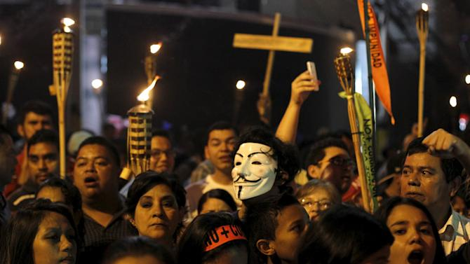 A man, wearing a Guy Fawkes mask, takes part in a march to demand the resignation of Honduras' President Juan Hernandez in Tegucigalpa
