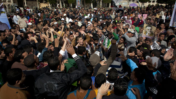 FILE - In this Friday, Feb. 22, 2013 file photo, Egyptian Ultras, hard-core soccer fans, chant anti-president Mohammed Morsi slogans while attending a rally in front of the provincial government headquarters, unseen, in Port Said, Egypt. Egypt's streets have turned into a daily forum for airing a range of social discontents from labor conditions to fuel shortages and the casualties of myriad clashes over the past two years. Newly called parliamentary elections hold out little hope for plucking the country out of the turmoil and if anything, are likely to just fuel unrest and push it toward economic collapse. (AP Photo/Nasser Nasser, File)