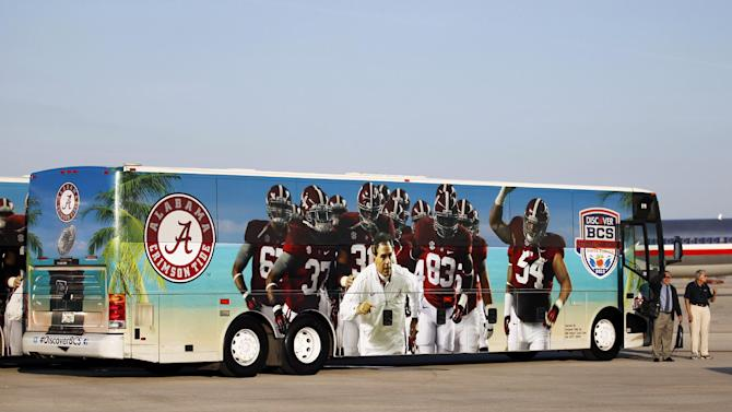 A bus with the image of head coach Nick Saban and players on the side prepares to take the team from Miami International Airport, Wednesday, Jan. 2, 2013, in Miami. Alabama is scheduled to play Notre Dame in the BCS national championship NCAA college football game next Monday in Miami. (AP Photo/Wilfredo Lee)