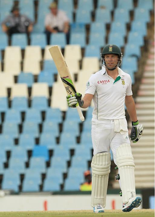 South Africa's batsman AB de Villiers, raises his bat after reaching a half century on the second day of their their cricket test match against Australia at Centurion Park in Pretoria, South Afric