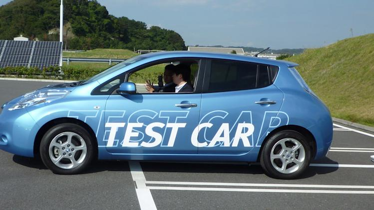 In this Friday, Oct. 12, 2012 photo, a Nissan staff driver, left, of a Leaf electric vehicle, releases his hands from the steering wheel as he shows automated steering parking technology at the Japanese automaker's test ground in Yokosuka, south of Tokyo. In the demonstration the vehicle turned on its own and backed into a charging station. The car is potentially capable of parking itself, even without a driver, according to Nissan. (AP Photo/Yuri Kageyama)