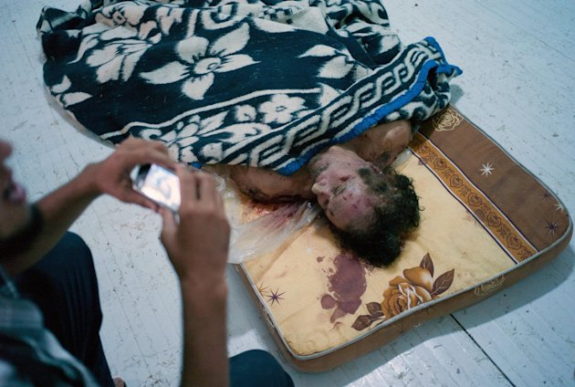 A man photographs the body of Libyan dictator Moammar Gadhafi on a mattress in a commercial freezer at a shopping center in Misrata, Libya, Saturday, Oct. 22, 2011. A military spokesman says Libya&#39;s transitional government will declare liberation on Sunday after months of bloodshed that culminated in the death of longtime leader Gadhafi. (AP Photo/David Sperry)