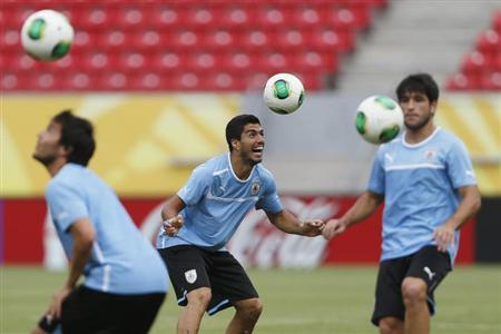 Uruguay's Luis Suarez (C) heads a ball during a training session ahead of their Confederations Cup soccer match against Tahiti on Sunday at the Arena Pernambuco Stadium in Recife, June 22, 2013. REUTERS/Ivan Alvarado/Files