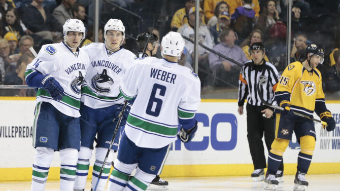 Vancouver Canucks left wing Alex Burrows (14) is congratulated by Bo Horvat (53) and Yannick Weber (6), of Switzerland, after Burrows scored a goal against the Nashville Predators in the third period of an NHL hockey game Tuesday, March 31, 2015, in Nashville, Tenn. At right is Predators center Craig Smith (15). The Canucks won 5-4 in a shootout. (AP Photo/Mark Humphrey)