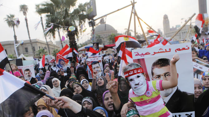 """Supporters of Egypt's ousted President Mohammed Morsi wave his posters and national flags as one carries her daughter with a mask of him during a protest in Nahda Square, where protesters have installed their camp near Cairo University in Giza, southwestern Cairo, Egypt, Tuesday, Aug. 13, 2013. Egypt's interim president swore in 20 new provincial governors on Tuesday, a move that reinforces the new leadership's authority and removes all Muslim Brotherhood members previously installed in the posts by Mohammed Morsi before his ouster as president. The Arabic on the posters reads, """"Yes for legitimacy, no for coup."""" (AP Photo/Amr Nabil)"""