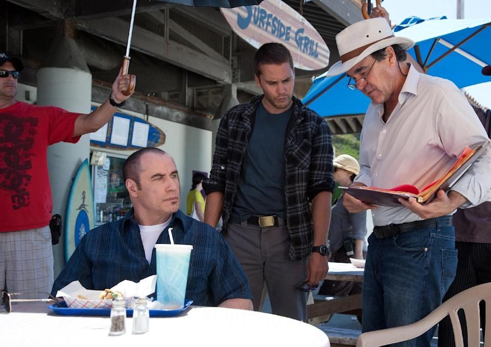 "This image released by Universal Pictures shows actors John Travolta, left, and Taylor Kitsch, center, with director Oliver Stone during the filming of ""Savages."" (AP Photo/Universal Pictures, Francois Duhamel)"