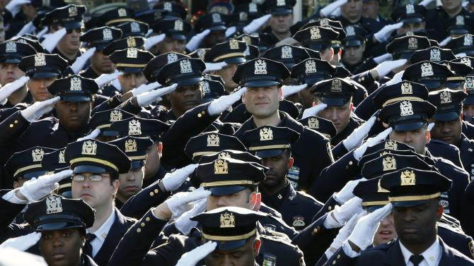 Police salute outside the Christ Tabernacle Church as the casket of slain NYPD officer Ramos is carried from the church following his funeral service in New York