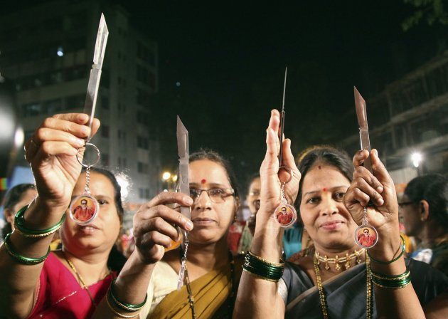Women pose with knives, distributed by India's radical Hindu nationalist party Shiv Sena, in Mumbai January 23, 2013. The Shiv Sena, an ally of the main opposition BJP, has handed out kitchen knives and chilli powder to women in Mumbai following the gang rape of a student in Delhi that ignited a national debate on the best way to tackle sex crimes. Pictures of Bal Thackeray, founder of the Shiv Sena, dangle from key rings attached to the knives. Picture taken January 23, 2013. REUTERS/Stringer (INDIA - Tags: CRIME LAW CIVIL UNREST TPX IMAGES OF THE DAY POLITICS)