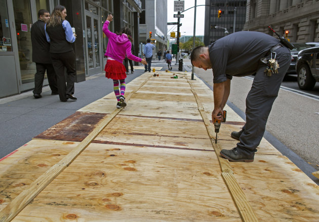 A maintenance worker named Vitto attaches plywood to a sidewalk grate at the 2 Broadway building of Lower Manhattan in New York, Sunday, Oct. 28, 2012, as a child walks along the temporary structure. 