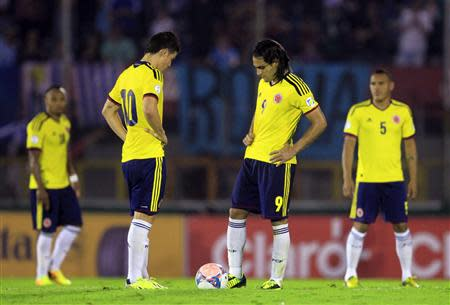 Colombia's players restart the game after conceding a goal to Uruguay's during their 2014 World Cup qualifying soccer match in Montevideo