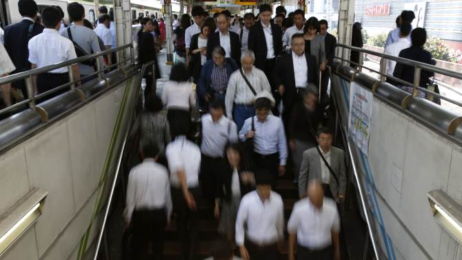 People walk down stairs in a train station in Tokyo's business district
