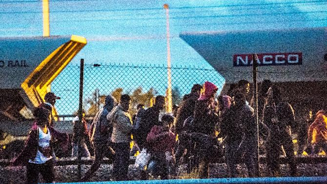 Migrants walk on the train tracks in the direction of the Eurotunnel terminal in Fréhun on August 11, 2015