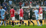 Manchester City's Vincent Kompany, left, is shown a red card by referee Chris Foy, third from right, during their FA Cup third round soccer match against Manchester United at the Etihad Stadium, Manchester, England, Sunday, Jan. 8, 2012. (AP Photo/Tim Hales)