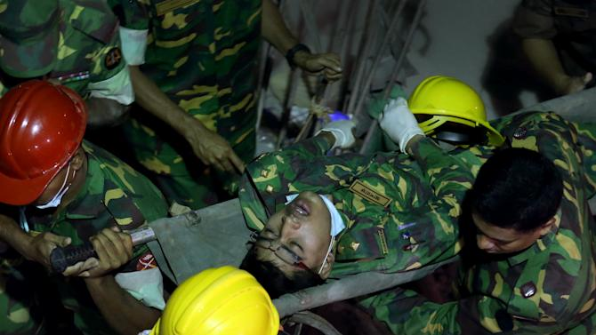 A soldier is evacuated from a fire which broke out in a garment factory building which collapsed Wednesday in Savar, near Dhaka, Bangladesh, Sunday April 28, 2013. A fire broke out late Sunday in the wreckage of the garment factory that collapsed last week in Bangladesh, with smoke pouring from the piles of shattered concrete and some of the rescue efforts forced to stop. The fire came four days after the collapse, as rescuers were trying to free a woman they found trapped in the rubble.(AP Photo/Wong Maye-E)
