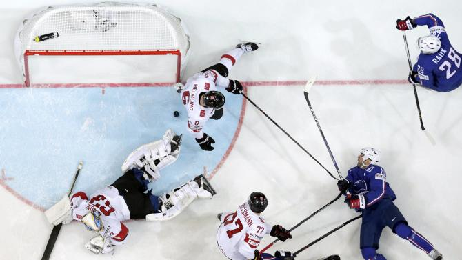 France's Meunier tries to score past Switzerland's Helbling, Grossmann and goaltender Genoni during their Ice Hockey World Championship game at the O2 arena in Prague